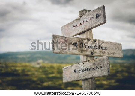 Solutions, troubles and setbacks text on wooden signpost outdoors in nature. Business, corporate, leadership concept. #1451798690