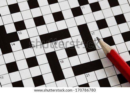 Solving a crossword puzzle with red pencil