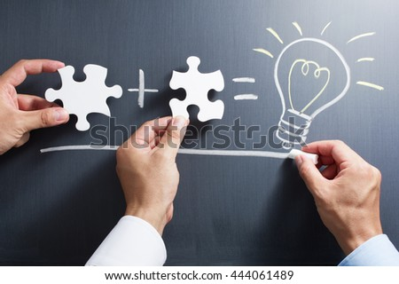 Solving puzzle together. Drawing light bulb on blackboard. Combining the wisdom for developing new idea.  Foto d'archivio ©