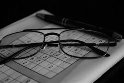 Solving Sudoku sharpens the brain - hobby  - glasses, pen