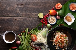Som Tam Thai - Papaya Salad Thai Food Style on wooden table background. Thai Food Concept. Top View