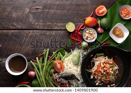 Som Tam Thai - Papaya Salad Thai Food Style on wooden table background. Thai Food Concept. Top View