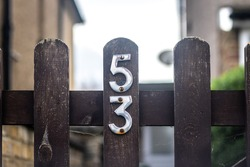 Somber and dark is number 53 on a wooden gate