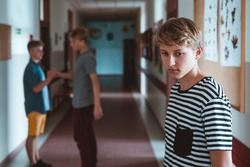 Somber boy is standing in the school corridor. Behind him are two classmates