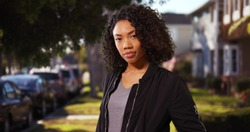 Somber modern African-American woman standing outside in residential area