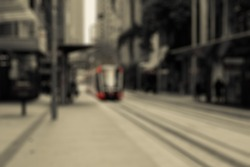 Sombre and gloomy city street perspective with a bright red tram coming to the camera. City blurry background