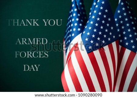 some american flags and the text thank you and armed forces day against a dark green background