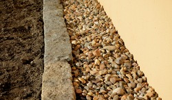 some areas in the city have only an infiltration and aesthetic function. mulched pebbles are light brown and are in the gutter sidewalk around the building. Granite curbs separate them from the lawn
