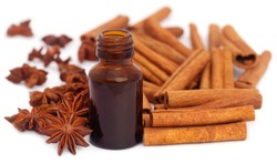 Some aromatic cinnamon with star anise and essential oil in a bottle