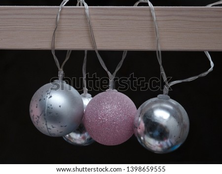 Some baubles hanging from a fooden frame. #1398659555