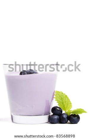 some blueberries with melissa near a milkshake with blueberries on white background
