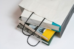 some books inside a white paper bag on the table