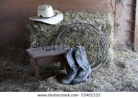 Some boots, a hat, a rope, and a bale of hay.
