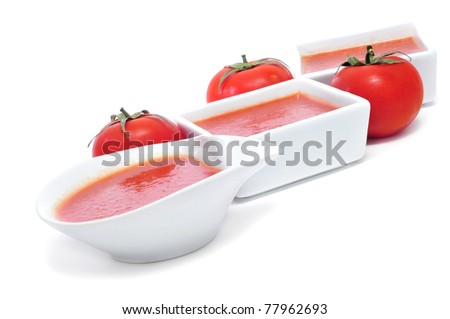 some bowls with gazpacho on a white background