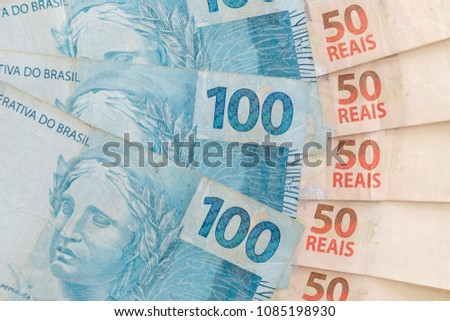 Some brazilian real (BRL) notes to show wealth, profit or a good investment. Money from Brazil. Bills of a hundred reais and fifty reais.
