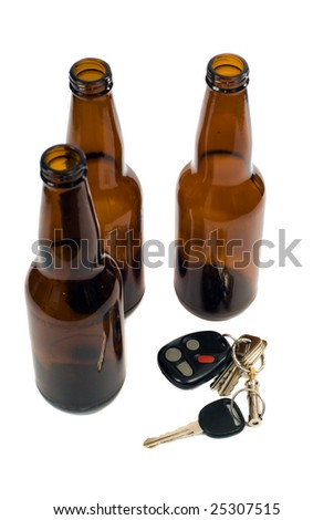 Some car keys shot alongside some empty beer bottles, isolated against a white background