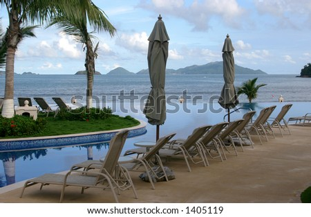 Some chairs on a beach front pool waiting for you to sit on them #1405119