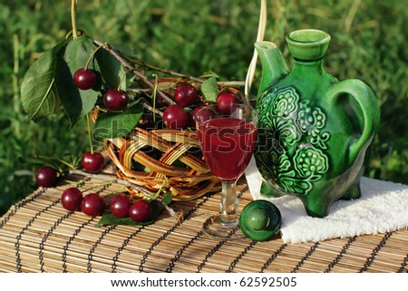 Some cherries, green jug and glass of cherry brandy on bamboo mat.