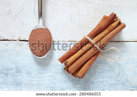 Some cinnamon sticks tied with a natural rope. Next, a spoon with some powdered cinnamon. All on a white wooden table. Top view