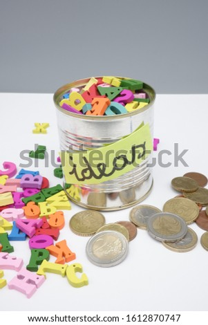 Some coins with some colored letters and a tin can,with ideas written on it,full of other letters. Concept of good ideas make money