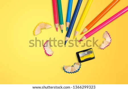 some colored pencils of different colors and a pencil sharpener and pencil shavings on a white background
