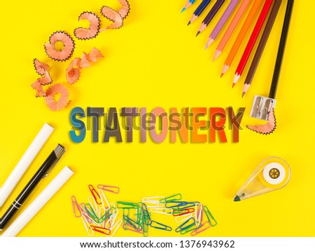 Some colored pencils of different colors and a pencil sharpener and pencil shavings on the yellow. Stationery