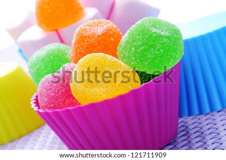some colorful bowls with candies of different colors on a purple woven surface