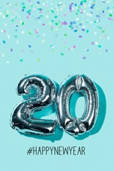 some confetti, two silvery number-shaped balloons forming the number 20, as the new year, and the hashtag happynewyear against a blue background