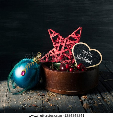 some cozy christmas ornaments in a wooden tray and a heart-shaped black signboard with the text feliz navidad, merry christmas written in spanish, on a gray rustic wooden surface, slightly lighted