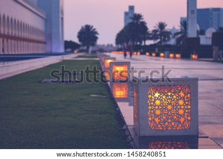Some decorations in the big garden of Sheikh Zayed Grand Mosque. Cubes are illuminated with soft lights next to the green grass, with palm trees in the background. Holy place in Abu Dhabi, Emirates.
