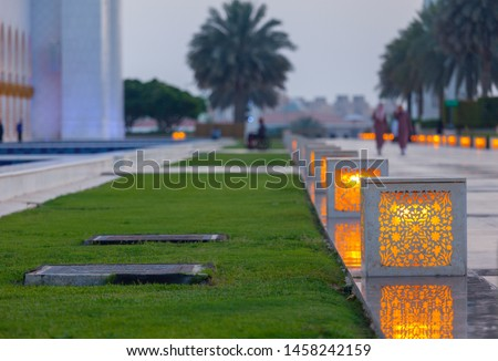 Some decorations in the big garden of Sheikh Zayed Grand Mosque. Cubes are illuminated with soft lights next to the green grass, with palm trees in the background. Holy place in Abu Dhabi.