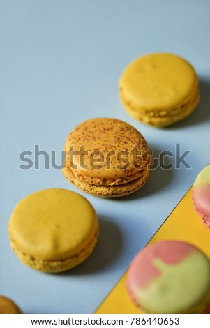 some delicious macarons of different flavors on a blue and orange background #786440653