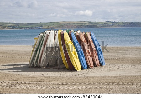 some different kayaks stood on the beach