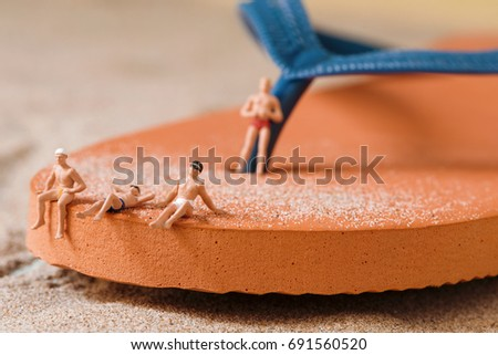 some different miniature men wearing swimsuit relaxing on an orange flip-flop on the sand of the beach