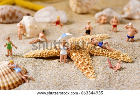 some different miniature people wearing swimsuit relaxing next to some seashells and a starfish on the sand of the beach