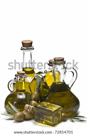 Some different olive oil pourers and some green olives isolated on a white background. - stock photo