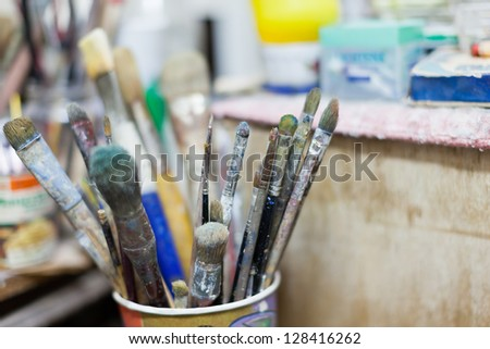 some dirty paintbrushes in a cup