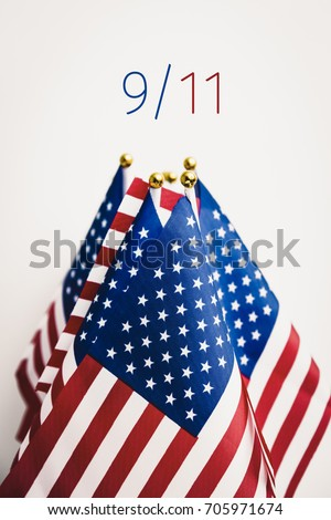 some flags of the United States and the text 9/11 for September the 11th against an off-white background