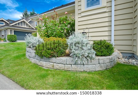 Some flowers and nicely trimmed bushes on the leveled front yard flowerbed. Landscape design.