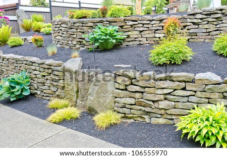 Some Flowers And Nicely Trimmed Bushes On The Leveled With Stones ...