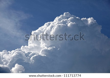 Some fluffy white clouds in a bright blue sky.