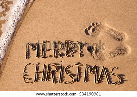 some foot prints and the text merry christmas written in the sand of a beach - Merry Christmas Beach Images