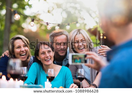 Some friends in their forties gathered around a table in the garden for a good time. A man takes a picture of a group of friends