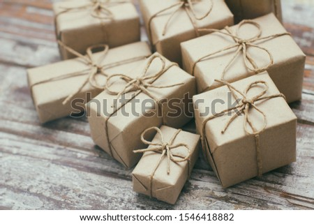 Some gift boxes wrapped in brown craft paper and tie hemp cord. Decorative wooden background. Your text space. Set of presents. Christmas presents. Holiday mood. New year decor. Gift exchange.