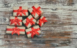 Some gift boxes wrapped in brown craft paper and tie red satin ribbon. Decorative wooden background. Your text space. Set of presents.