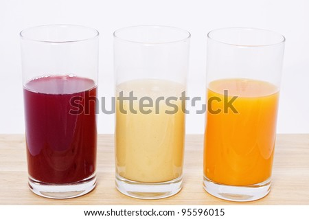 Some glass with juice of different fruit in white background - stock photo