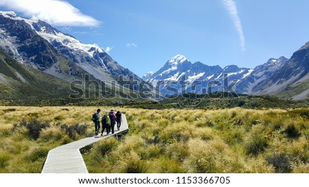 Some hikers visiting the beautiful Hooker Valley. This breathtaking place is located in Aoraki, New Zealand. It is a famous tourist attraction. Visitors can enjoy alpine streams, glacier and lake. #1153366705