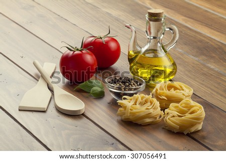 Some ingredients in a wooden table for cooking Italian pasta: tomatoes, nests ribbons pasta, olive oil, peppermint and pepper