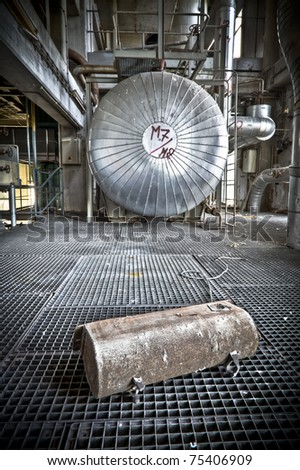 Some kind of container laying in front of this huge silo. Picture taken at an abandoned power station. A grungy industrial scene.