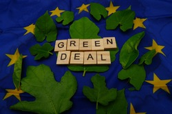 Some leaves,with a wooden inscription,green deal,above a European flag. Concept of fighting climate change on earth